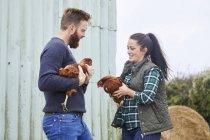 Junges Paar auf der Hühnerfarm halten Hühner — Stockfoto