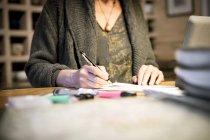 Обрезанное изображение женщины, работающей за столом в офисе — стоковое фото