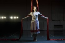 Portrait of young female aerial acrobat poised between red silk ropes — Stock Photo