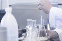 Échantillon de pipetage scientifique dans bécher en laboratoire — Photo de stock