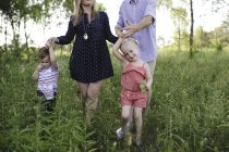 Mid adultos pais passeando no prado menino e menina — Fotografia de Stock