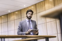 Businessman using digital tablet touchscreen on office balcony — Stock Photo