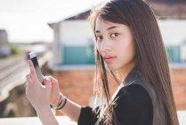 Ritratto di giovane donna sulla terrazza sul tetto della città con smartphone in mano — Foto stock