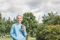 Female runner with takeaway coffee in park, Reykjavik, Iceland — Stock Photo