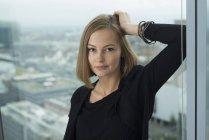 Портрет уверенной молодой предпринимательницы, опирающейся на оконную раму офиса — стоковое фото