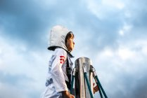 Portrait of boy in astronaut costume gazing out from top of climbing frame against dramatic sky — Stock Photo