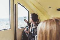 Joven tomando fotografías de teléfonos inteligentes a través de la ventana funicular, Como, Italia - foto de stock