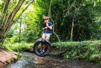 Мальчик на шине, использующий реку — стоковое фото