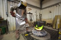 Male foundry worker heating bronze ingot over furnace in bronze foundry — Stock Photo