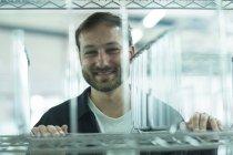 Homem empurrando gaiola de rolo sorrindo — Fotografia de Stock