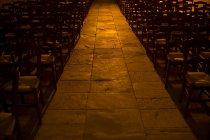Filas de sillas en la iglesia con pasillo iluminado - foto de stock