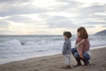 Mother and daughter on beach looking at ocean — Stock Photo