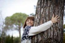 Vue latérale d'arbre étreindre femme — Photo de stock