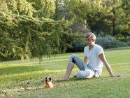 Молодой человек отдыхает на траве, отдыхает от физических упражнений — стоковое фото