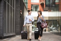 Young businessman and woman with wheeled suitcases walking and talking, London, UK — Stock Photo