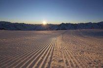 Sonne beleuchtete verschneiten Tal und Berge bei Sonnenuntergang — Stockfoto