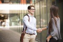 Бизнесмен и женщина пожимают руки за пределами офиса, Лондон, Великобритания — стоковое фото