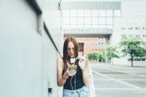 Молодая женщина, прислонившись к стене, читает смс на смартфоне — стоковое фото