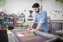 Jeune imprimante mâle à l'aide de raclette en imprimerie studio — Photo de stock