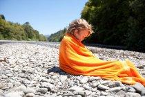 Garçon dans serviette assis sur les rochers — Photo de stock