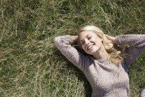 Portrait de jeune femme allongée sur l'herbe — Photo de stock