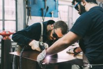 Metalwork team cutting copper with welding torch in forge workshop — Stock Photo