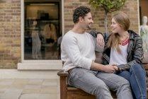 Romantico giovane coppia seduta su panchina, Kings Road, Londra, Regno Unito — Foto stock