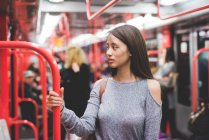 Young woman traveling on train carriage looking over her shoulder — Stock Photo