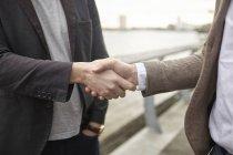 Средний обзор двух бизнесменов, пожимающих руки на набережной, Лондон, Великобритания — стоковое фото