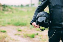 Mittleren Bereich des männlichen Motorradfahrer stehen auf einer Brache mit Helm — Stockfoto