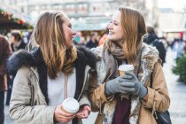 Two young female friends having takeaway coffee at christmas market — Stock Photo