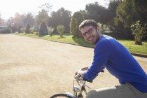 Середині дорослої людини, що сидить на велосипеді в парку, дивлячись камера посміхаючись — стокове фото
