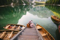 Woman relaxing on pier, Lago di Braies, Dolomite Alps, Val di Braies, South Tyrol, Italy — Stock Photo