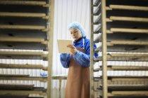 Female worker using digital tablet in underground tunnel seed tray nursery, London, UK — Stock Photo