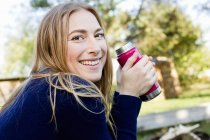 Mid adult woman drinking hot drink — Stock Photo