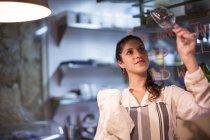Владелец ресторана проверяет бокал вина на кухне — стоковое фото