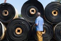 Чоловік дивиться на рулонах матеріал у дворі Кастор колісний завод з виробництва, Ballenstedt, Німеччина — стокове фото
