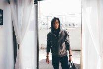 Человек, стоящий в дверях и несущий холдалл — стоковое фото