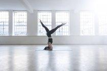 Frau im Tanzstudio macht Kopfstand — Stockfoto
