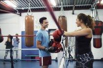 Женщина-боксер, опирающаяся на боксерские веревки, разговаривает с боксером — стоковое фото