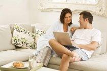 Couple senior sur canapé navigation portable et petit déjeuner — Photo de stock
