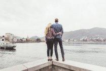Vista posterior de la situación de la joven pareja en la pared del puerto mirando, lago de Como, Italia - foto de stock