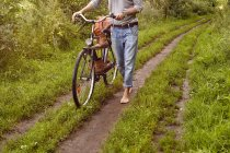 Neck down view of man pushing bicycle on rural dirt track — Stock Photo