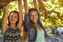 Портрет двух подруг на улице, висящих на ветке дерева — стоковое фото