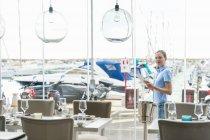 Donna all'esterno del ristorante marina utilizzando la tavoletta digitale, Maiorca, Spagna — Foto stock