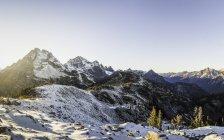 Couvert de neige des pics montagneux au soleil avec un ciel dégagé — Photo de stock