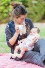 Mutter sitzt auf Decke und zeigt Baby-Mädchen Spielzeug — Stockfoto