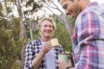 Два туриста-мужчины разговаривают за кофе в лесу, Дир Парк, Кейптаун, Южная Африка — стоковое фото