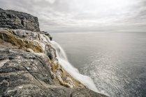 Bosdalafossur Cachoeira caindo do penhasco no oceano, Vágar, Faroe Islands — Fotografia de Stock