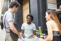 Cameriere che serve coppia in città marciapiede caffè — Foto stock